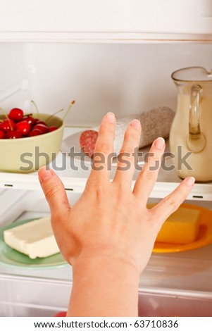 A young woman's hand reaching out for food from the refrigerator. - stock photo