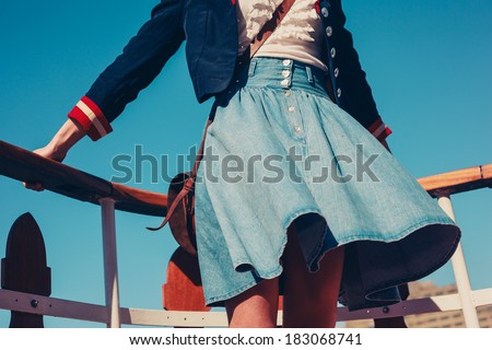 A young woman's skirt is blowing in the wind as she is standing on the deck of a boat cruising down the river - stock photo