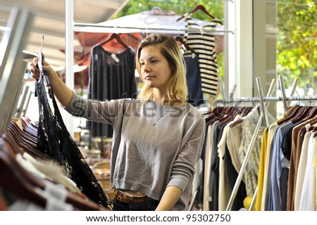 a young woman selects a dress from a well stocked rack in a clothing boutique - stock photo