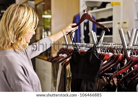 a young woman selects a little black dress from a rack of clothes in a fashion boutique - stock photo