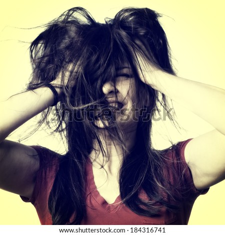 A young woman shaking her hair around in frustration, instagram style - stock photo