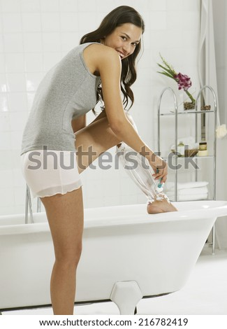 A young woman shaving her legs. - stock photo