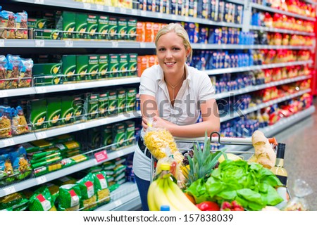 a young woman shopping in the supermarket. full cart. - stock photo