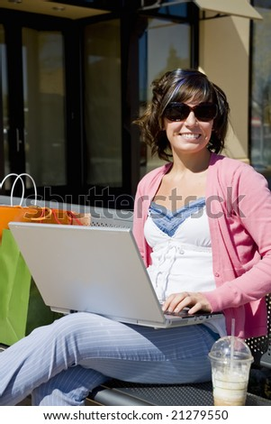 A young woman shopping sitting on a bench with laptop - stock photo