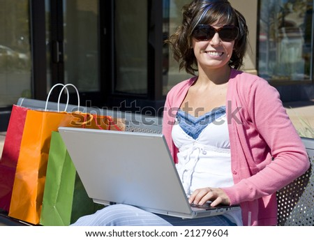 A young woman shopping sitting on her computer with bags - stock photo