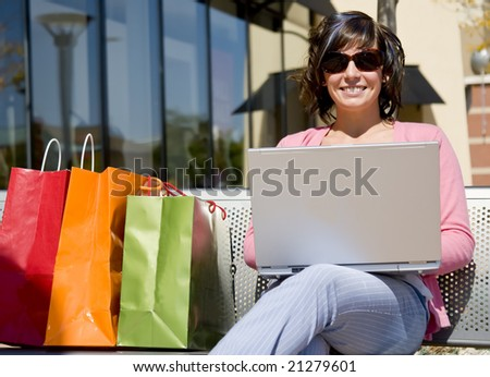A young woman shopping sitting with laptop - stock photo