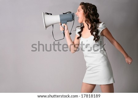 a young woman shouting into a megaphone - stock photo