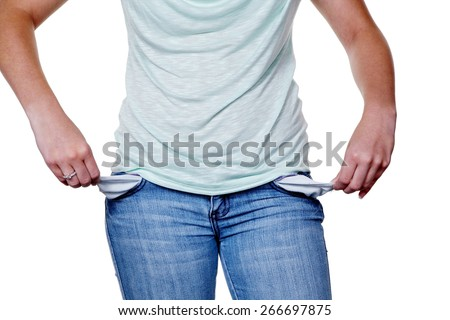 a young woman showing empty pockets of their jeans. symbolic photo for debt. - stock photo