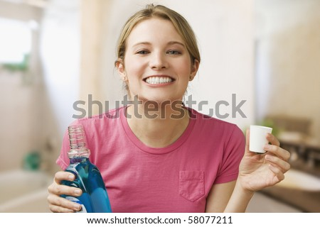 A young woman shows off her teeth while holding a bottle of mouthwash.  Horizontal shot. - stock photo