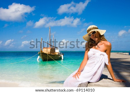 A young woman sits on a pier - stock photo