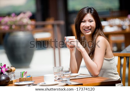 A young woman sitting alone at breakfast table at resort - stock photo