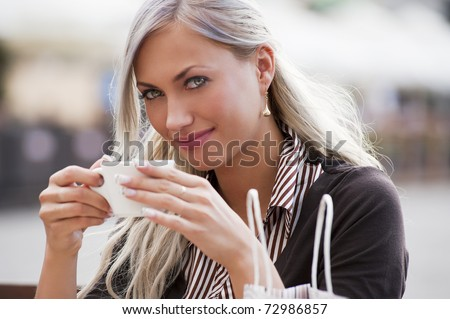 A young woman sitting alone in a cafe outdoor and drinking a cup of tea - stock photo