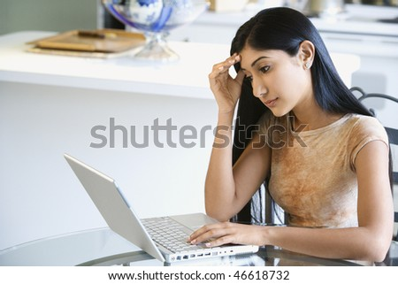 A young woman sitting at the kitchen table using a laptop. She has a worried expression on her face. Horizontal shot. - stock photo