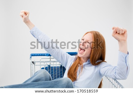 A young woman sitting in a large shopping cart and shouting for joy with her hands up in the air. - stock photo