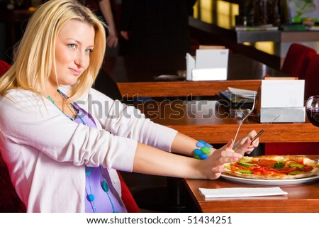 A young woman sitting in a restaurant. She is unhappy and pushing away pizza. Horizontal shot. - stock photo