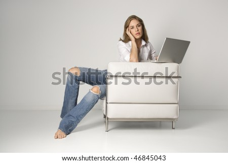 A young woman sitting in a white armchair with a laptop computer, looking at the camera. Horizontal shot. - stock photo