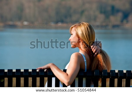 A young woman sitting on a bench by a lake - stock photo
