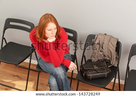 A young woman sitting on a chair in a waiting room, photographed from the top.