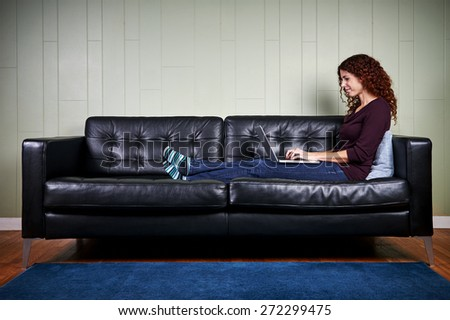 a young woman sitting on a sofa working on a laptop computer - stock photo