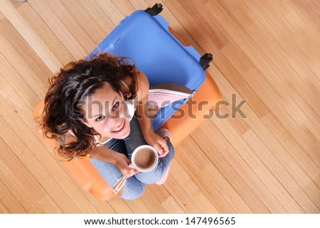 A young woman sitting on a stack of suitcases while drinking coffee and waiting for the departure to vacations. - stock photo