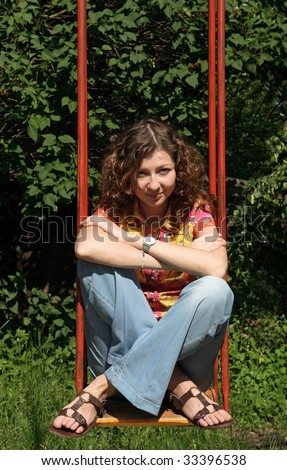 A young woman sitting on a swing in a park. - stock photo
