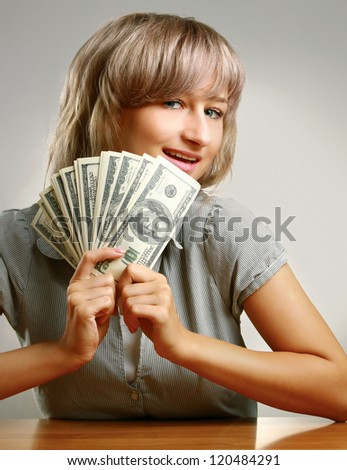 A young woman sitting on the desk and holding dollars, isolated on grey - stock photo