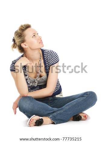 A young woman sitting on the floor, looking up - stock photo