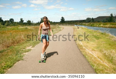 A young woman skateboards down a path near a river in Montana - stock photo