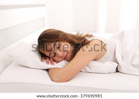 A Young Woman sleeping in bed with arm under pillow - stock photo