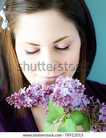 A young woman smelling a bunch of lilac flowers with her eyes closed.