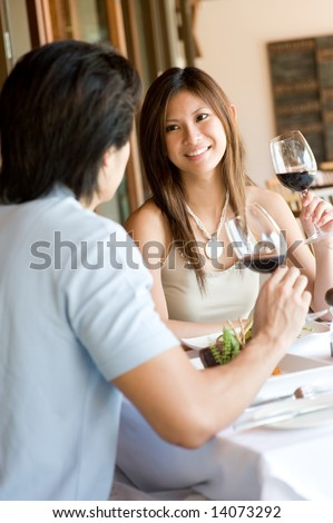 A young woman smiling whilst eating dinner at a restaurant