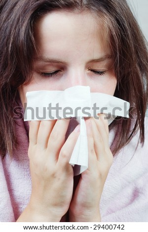 A young woman sneezing with a tissue in her hands