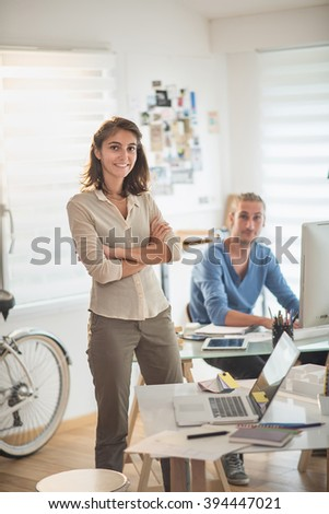 a young woman standing at her desk looking at camera and smiling, at background her colleague working on his computer, the office is modern and bright.Shot with flare