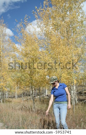 A young woman standing in field during yellow, autumn leaves
