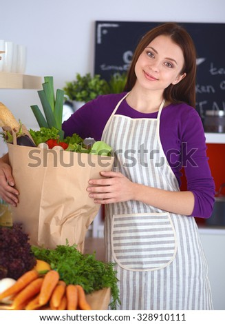 A young woman standing in her kitchen holding a bag of groceries.