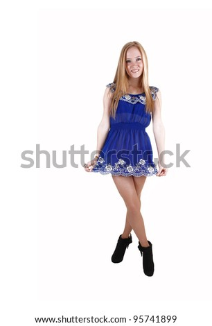 A young woman standing in the studio in a blue short dress and black boots with her long blond hair for white background. - stock photo