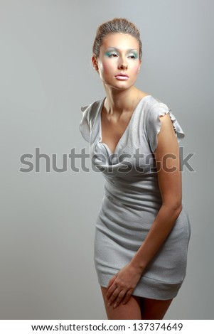 A young woman standing , isolated on  grey background