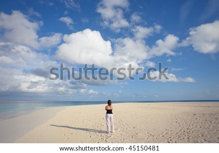 A young woman standing on a deserted beach