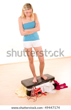 A young woman standing on an overstuffed and overflowing suitcase.  White background