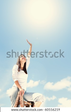 A young woman standing on ladders stretches her hand towards the sun. Slightly cross-processed image. - stock photo