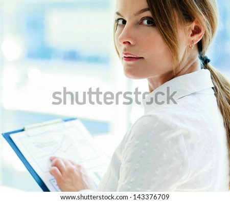 A young woman standing  with folder in office