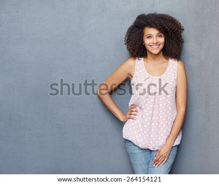 A young woman standing with her hand on her hip against a gray background - stock photo