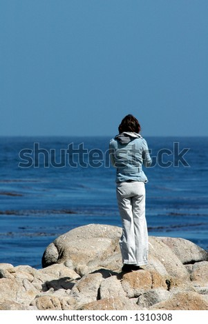 A young woman stands alone looking out into the Pacific ocean.