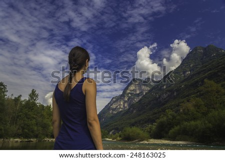 A young woman stands by a river looking at mountains. - stock photo