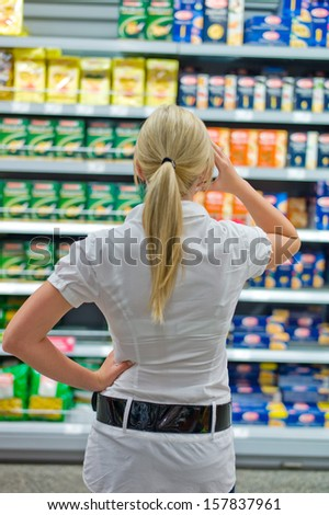 a young woman stands in front of a desperate shelf in the supermarket. excess supply of goods. - stock photo