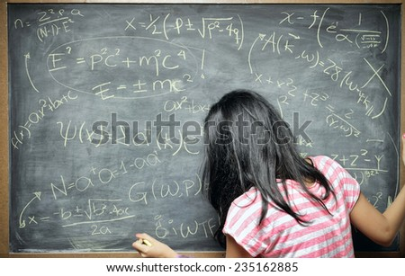 A young woman stands in front of blackboard filled with equations as if she were a genius or a teacher