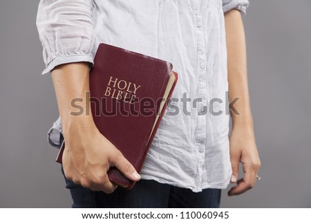 A young woman stands indoors casually holding a maroon bible to her side. - stock photo