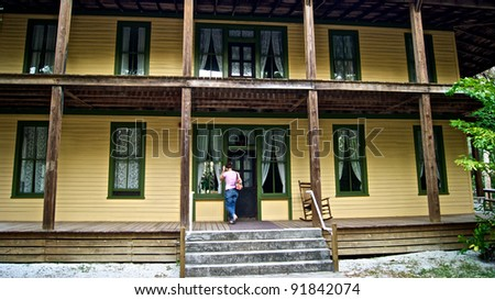 A young woman stands on the porch of an old wooden house built in early 1900's in historic area of estero florida. There is an old wooden rocking chair on porch. Koreshan state Park. - stock photo