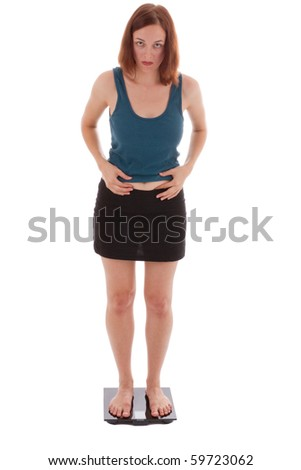 A young woman stands on the scales - stock photo