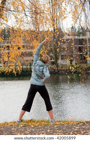 A young woman stretches by a river - stock photo